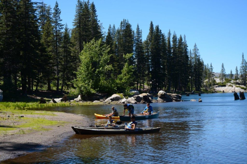 Candidate participants of White Stag Sierra paddle two canoes to the shore of Lake Sterling
